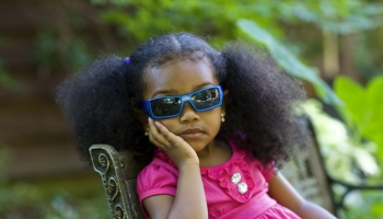 A little girl wearing sunglasses and a pink top