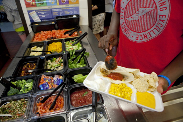 A child carry a tray with a healthy cafeteria lunch