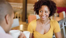 A woman smiling at her male coworker at a cafe