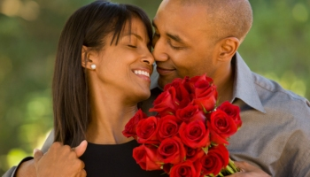 A smiling man giving red roses to a smiling woman
