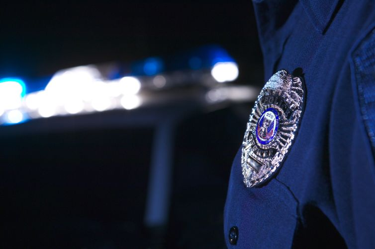 A close-up of a police officer's badge as he stands beside a police car