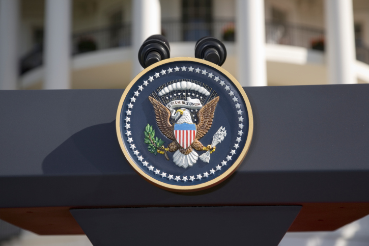 Presidential Seal on a podium in front of White House