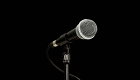 A microphone and a stand against a black background