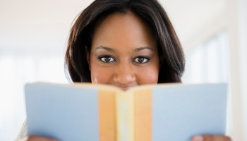 A happy woman holding a book in front of her face