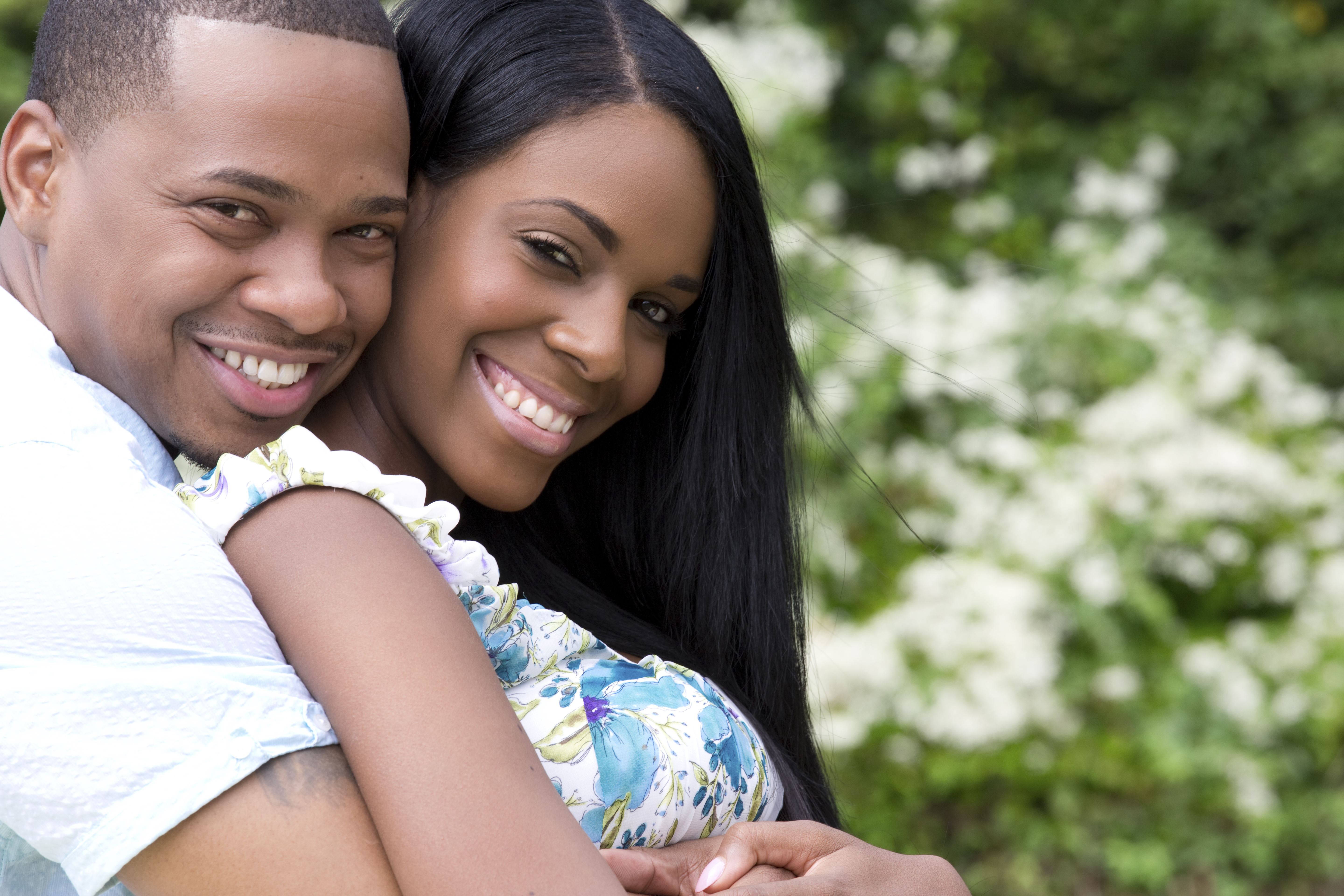 A smiling man hugging a smiling woman tightly