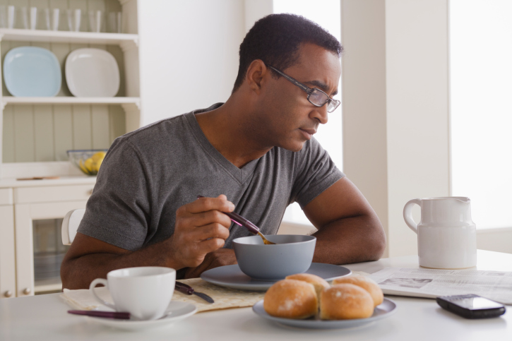 A man eating breakfast and reading newspaper