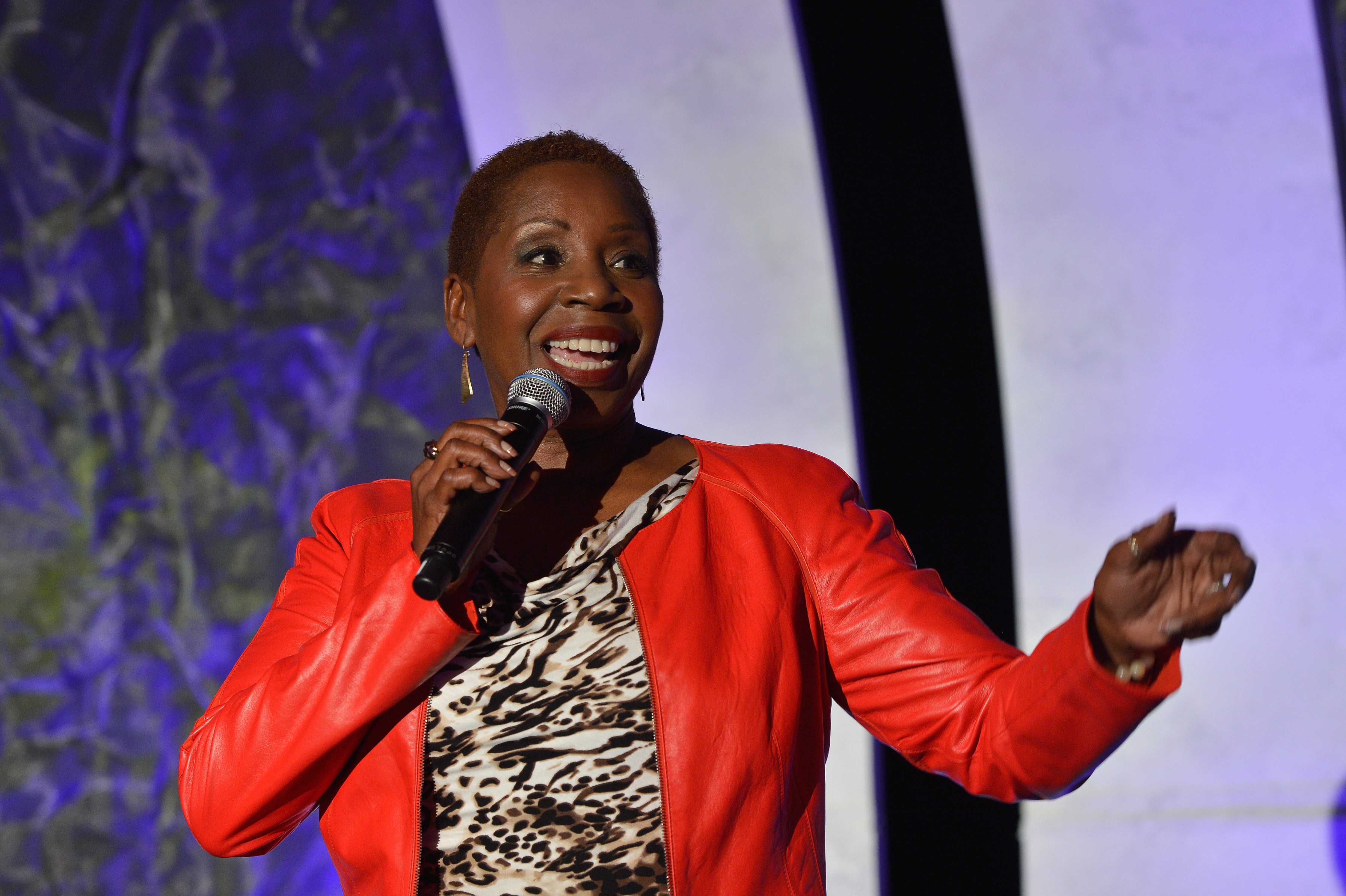 Iyanla Vanzant in a red jacket speaking at a conference.