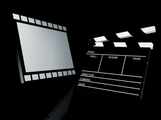 A clapper board and movie screen against black background