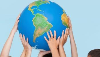 Five children's hands indoors touching a globe