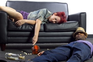 Two drunk people passed out on the floor and on a sofa