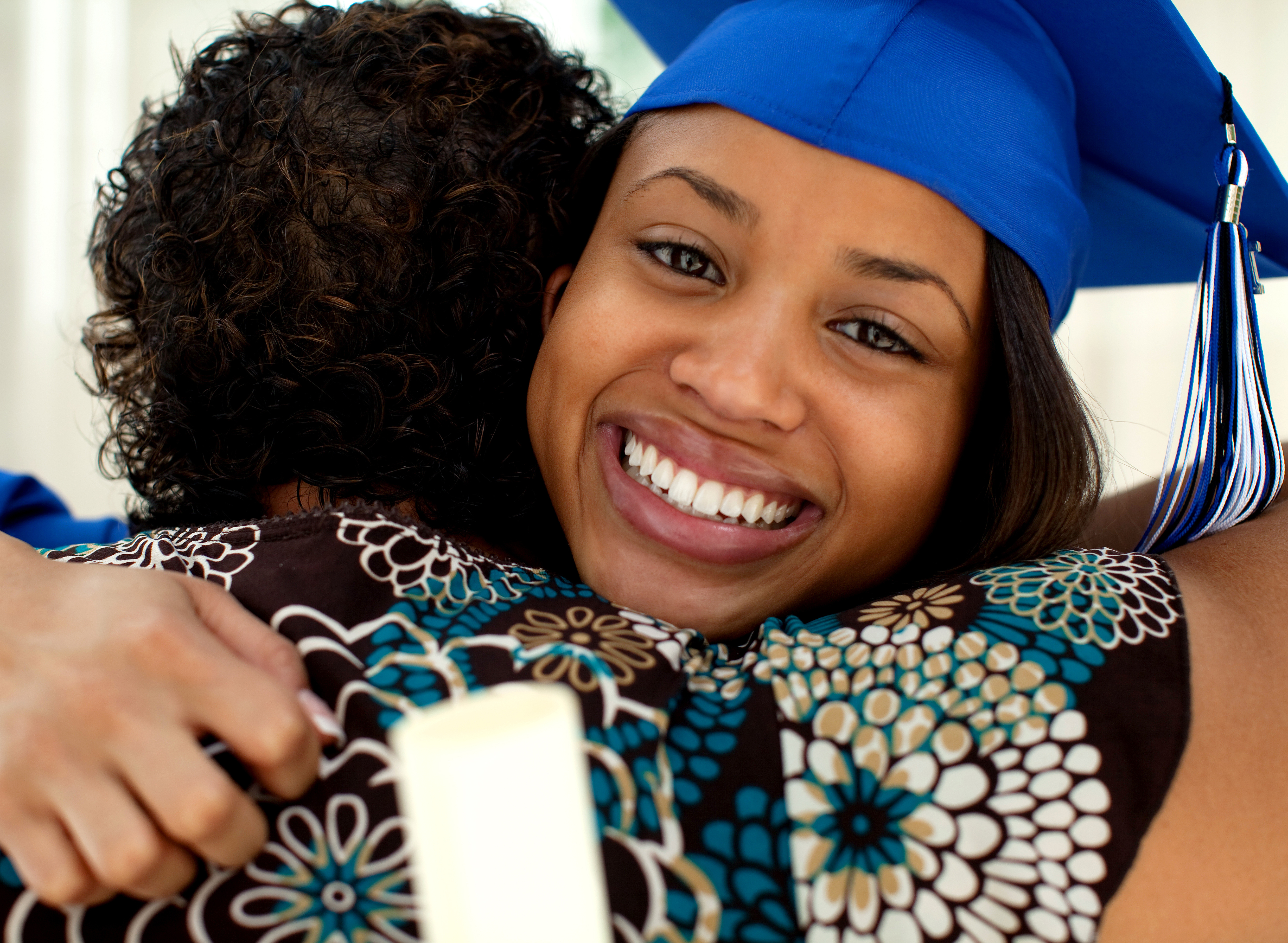 A smiling college graduate in a blue cap and gown hugging her mother