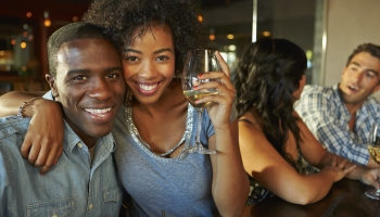 A smiling man and woman Enjoying Drinks At a Bar With Friends