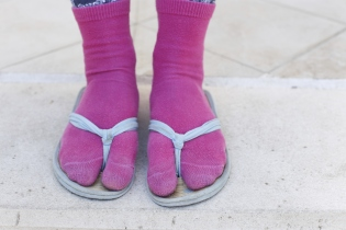 Someone wearing a pair of pink socks with flip flops
