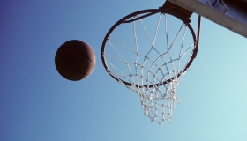 A basketball flying into a hoop on an outdoor court