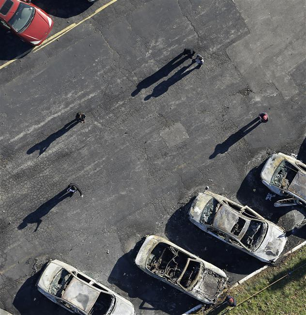 In this aerial photo,people look at a row of charred cars at a used car dealership, Tuesday, Nov. 25, 2014, in Dellwood, Mo.