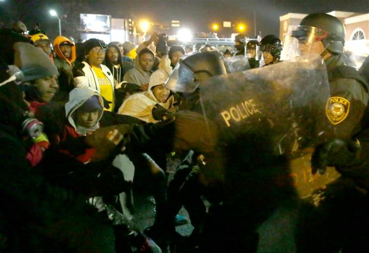 Police officers confront protesters Tuesday, Nov. 25, 2014, in Ferguson, Mo.
