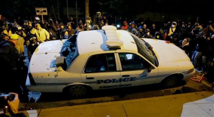 Protesters vandalize a police vehicle outside of the Ferguson city hall on Tuesday, Nov. 25, 2014, in Ferguson, Mo.