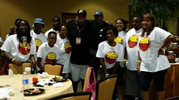 Comedian Chris Paul with a family at the Allstate Tom Joyner Family Reunion