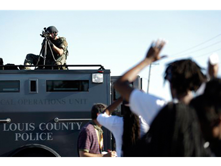 Police in riot gear watch protesters in Ferguson.
