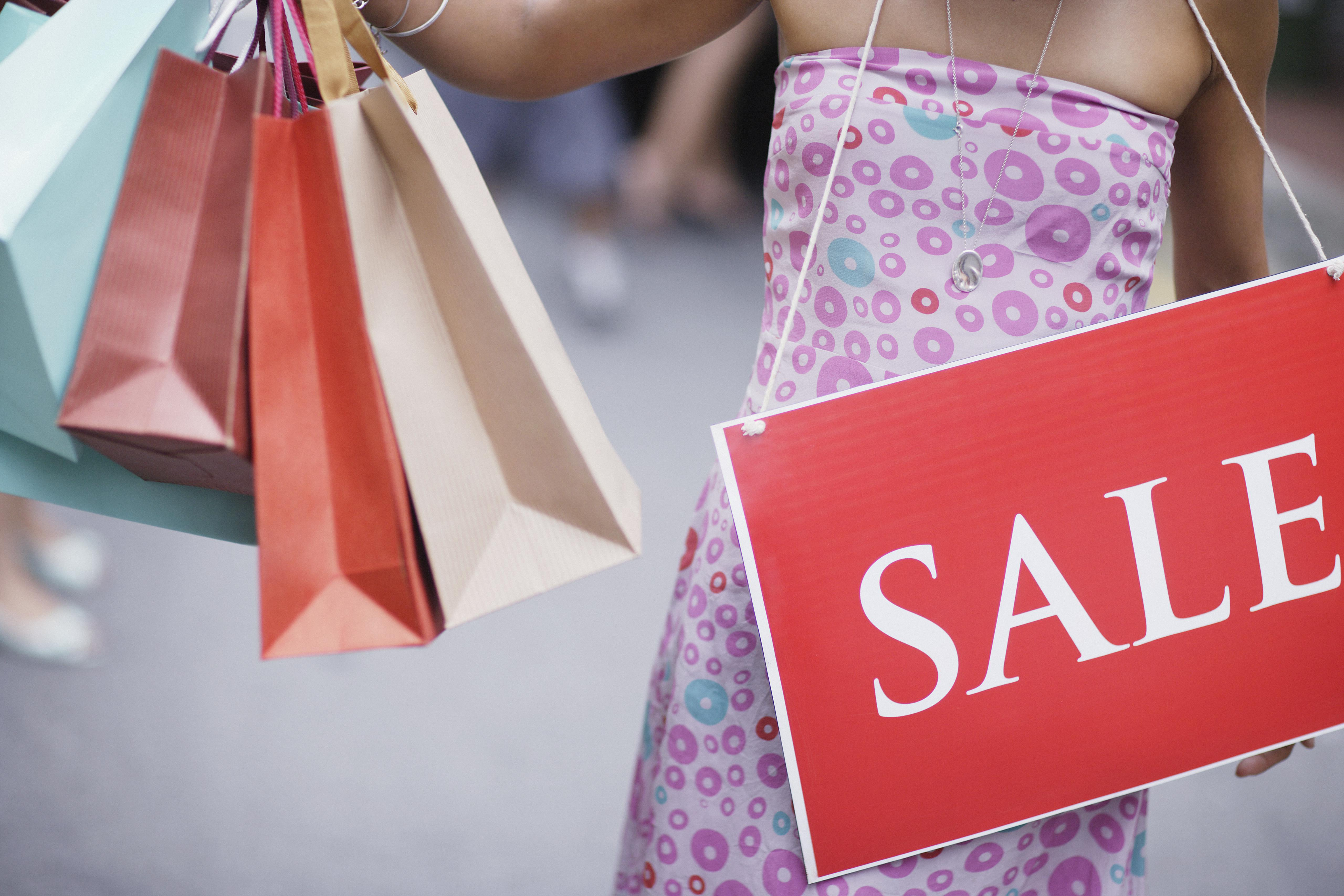 Woman outdoors holding shopping bags and wearing sale sign