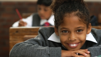 portrait of a young girl at school leaning on the desk