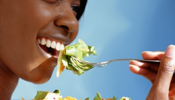 Young woman eating salad, close-up, side view