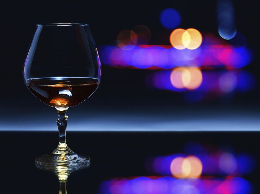 snifter with brandy on a dark background.