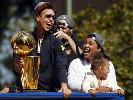 Golden State Warriors guard Stephen Curry, left, holds the Larry O'Brien Championship Trophy as he rides a bus with his daughter Riley, front right, and wife Ayesha as the procession turns onto Broadway in downtown Oakland, Calif., during a parade for the team's winning of the NBA basketball championship Friday, June 19, 2015. (Karl Mondon/San Jose Mercury News via AP) MAGAZINES OUT; NO SALES