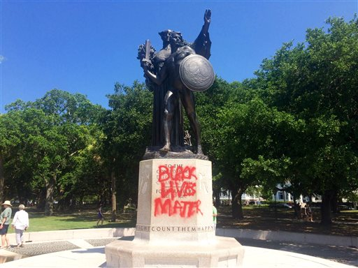 """A statue memorializing the Confederacy is spray-painted with the message """"Black Lives Matter"""" several days after a shooting at a historic black church Sunday, June 21, 2015, in Charleston, S.C. Police spokesman Charles Francis said city workers used a tarp to cover up the graffiti marking the stone pedestal beneath the statue. He said he didn't know when the graffiti was spray-painted there, but said it would be cleaned off. (AP Photo/WCSC-TV, Philip Weiss)"""