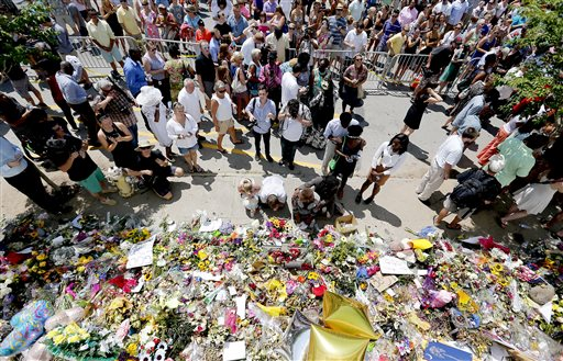 People pay respects outside Emanuel A.M.E. Church during a worship service, Sunday, June 21, 2015, in Charleston, S.C., four days after a mass shooting at the church claimed the lives of its pastor and eight others. (Paul Zoeller/The Post And Courier via AP)