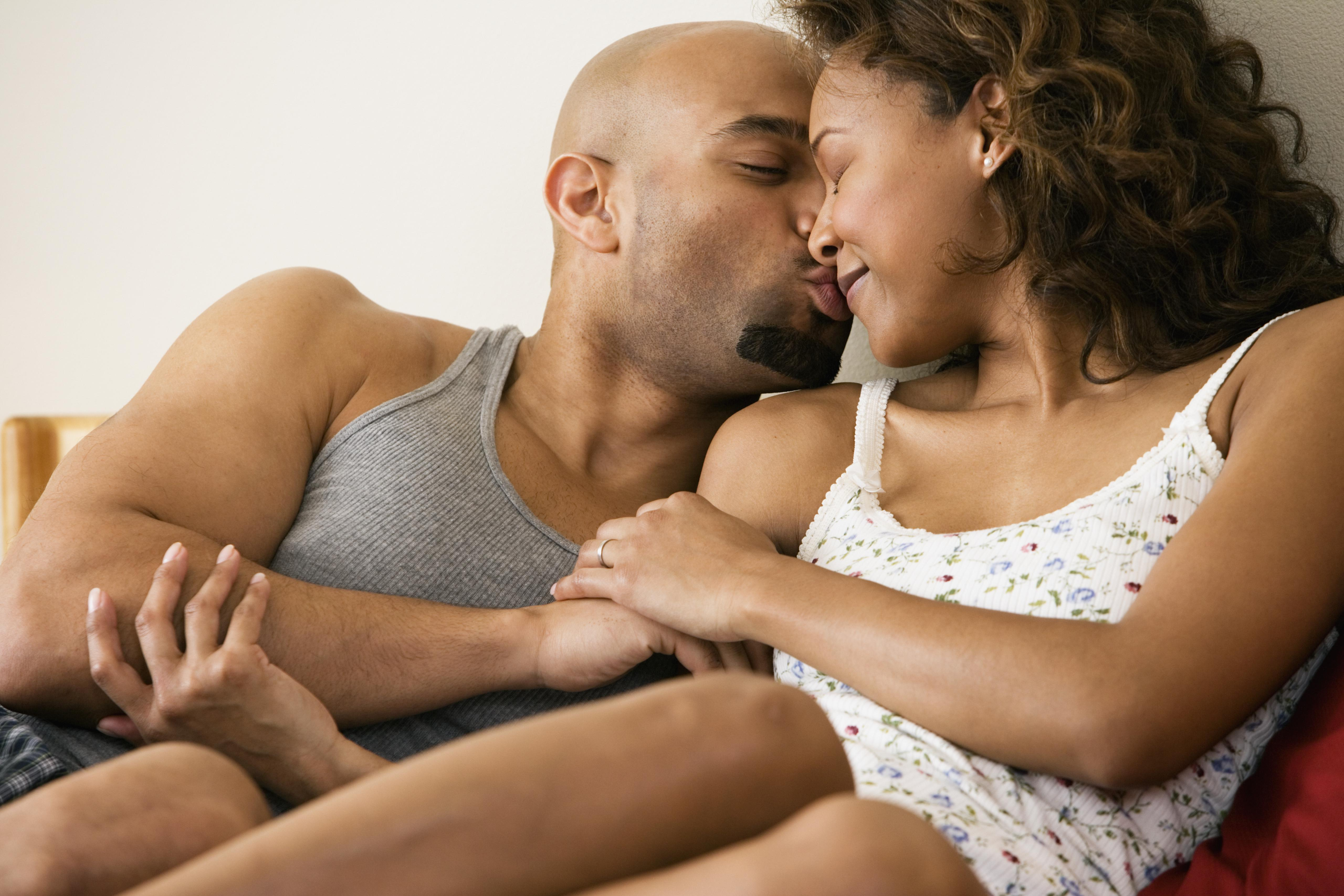 African couple kissing in bed