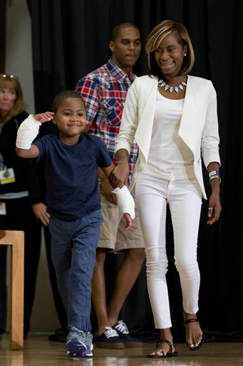 Double-hand transplant recipient eight-year-old Zion Harvey arrives to a news conference with his mother Pattie Ray Tuesday, July 28, 2015, at The Children's Hospital of Philadelphia (CHOP) in Philadelphia. Surgeons said Harvey of Baltimore who lost his limbs to a serious infection,  has become the youngest patient to receive a double-hand transplant. (AP Photo/Matt Rourke)