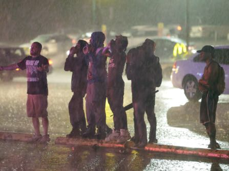 Protesters yell at police in the rain, Sunday, Aug. 9, 2015, in Ferguson, Mo. Sunday marks one year since Michael Brown was shot and killed by Ferguson police officer Darren Wilson. (AP Photo/Jeff Roberson)