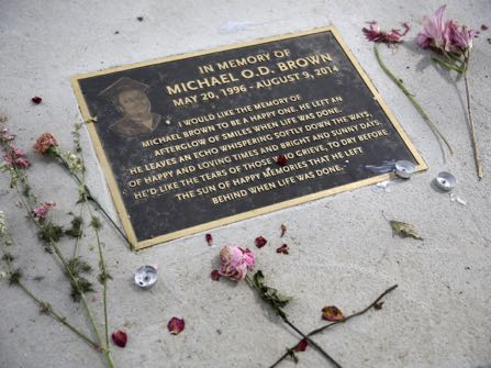 A memorial in memory of Michael Brown is seen in a sidewalk near where Brown was shot and killed is shown Saturday, Aug. 8, 2015, in Ferguson, Mo. Sunday will mark one year since Brown was shot and killed by Ferguson police officer Darren Wilson. (AP Photo/Jeff Roberson)