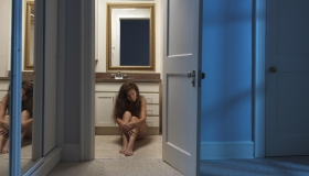 Woman sitting alone on a bathroom floor at night