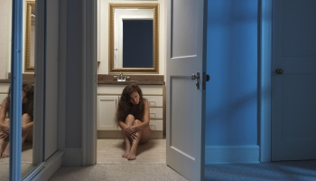 Woman sitting alone on a bathroom floor at night