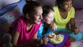 Preteen girls at sleepover watching tv, eating popcorn