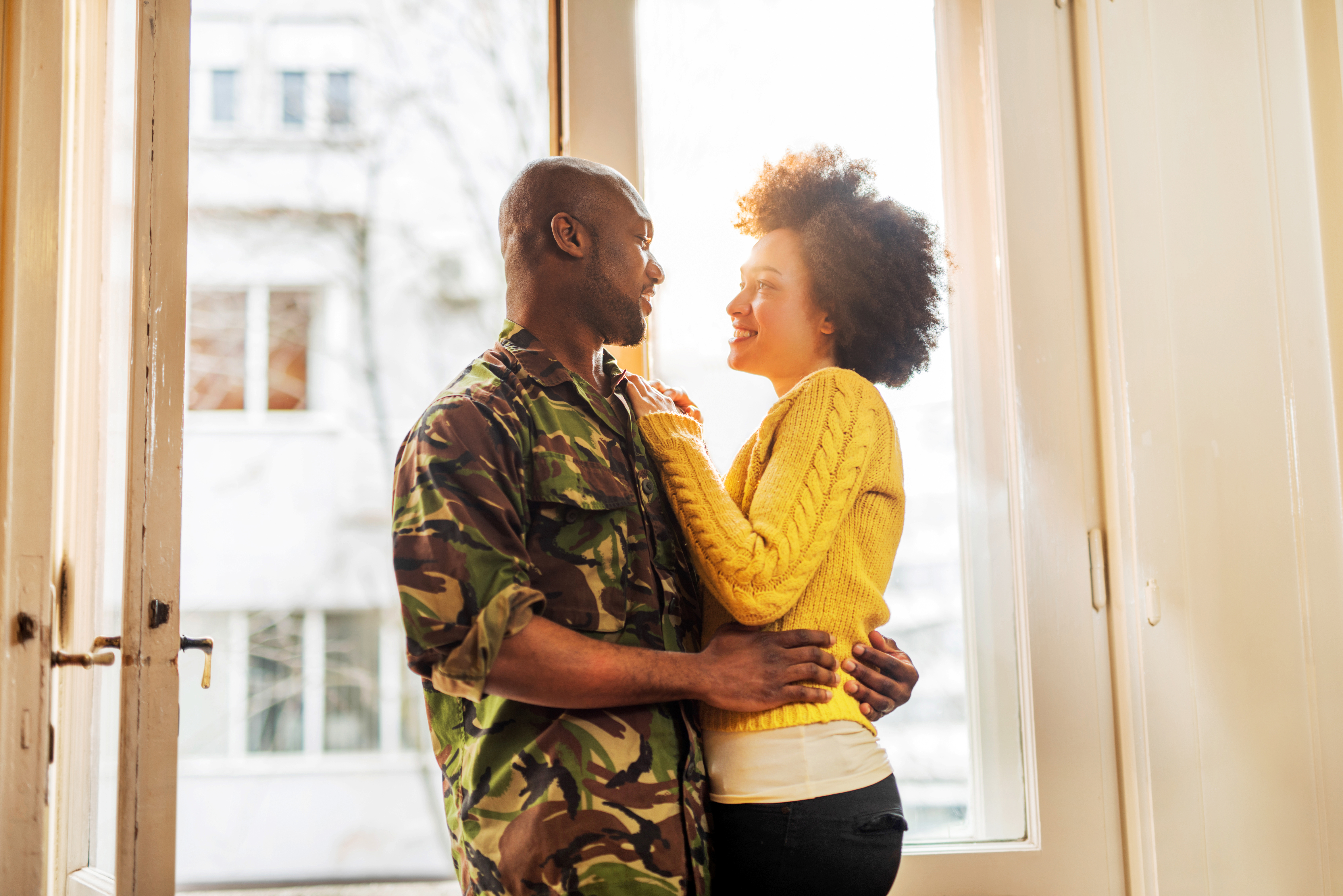 Happy African American soldier coming home to his wife.