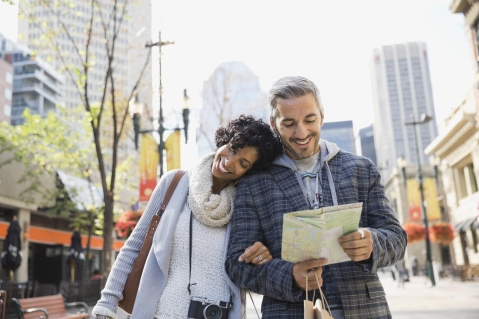 Loving couple with map walking on city street