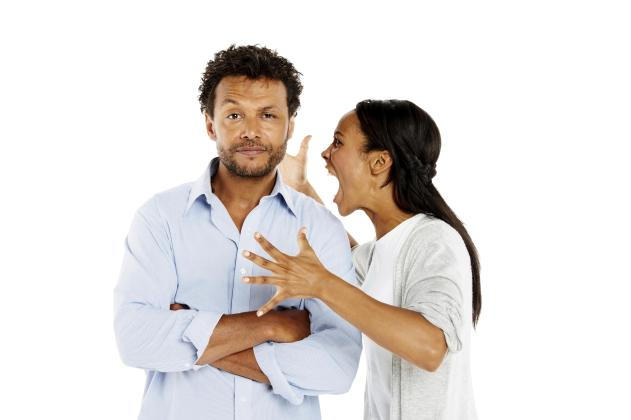 Portrait of young woman shouting at her boyfriend against white background