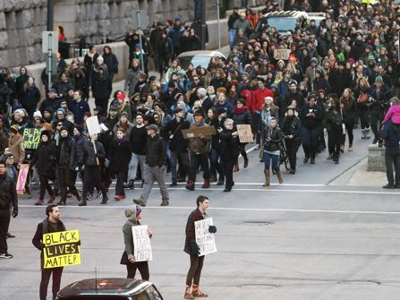 Black Lives Matter demonstrators and supporters march through downtown Minneapolis, Tuesday, Nov. 24, 2015, heading to the Federal Building. The fatal shooting of Jamar Clark, a black man, by a Minneapolis police officer, has pushed racial tensions in the city's small but concentrated minority community to the fore, with the police precinct besieged by the makeshift encampment and many protesters. (AP Photo/Jim Mone)
