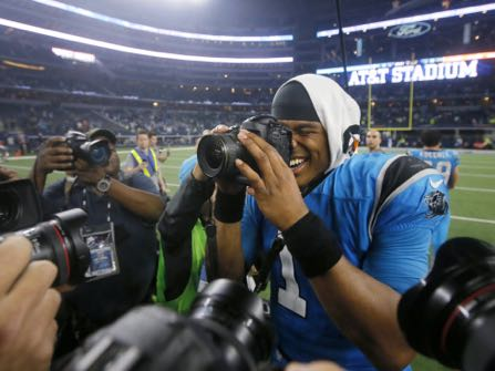 Carolina Panthers quarterback Cam Newton (1) takes photos of photographers taking his picture as he celebrates the team's 33-14 win over the Dallas Cowboys in an NFL football game, Thursday, Nov. 26, 2015, in Arlington, Texas. (AP Photo/Michael Ainsworth)