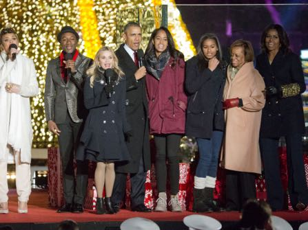 President Barack Obama, center, with from left to right, singer Andra Day, Aloe Blacc, actress Reese Witherspoon, daughters Malia and Sasha, mother-in-law Marian Robinson and first lady Michelle Obama, sing onstage during the National Christmas Tree Lighting ceremony at the Ellipse in Washington, Thursday, Dec. 3, 2015. (AP Photo/Pablo Martinez Monsivais)