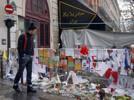 A member of the band Eagles of Death Metal, Jesse Hughes pays his respects to 89 victims who died in a Nov. 13 attack, at the Bataclan concert hall in Paris, France, Tuesday, Dec. 8, 2015. Members of the California rock band Eagles of Death Metal are back at the ravaged Paris theater where they survived a massacre by Islamic extremist suicide bombers. (AP Photo/Jacques Brinon)