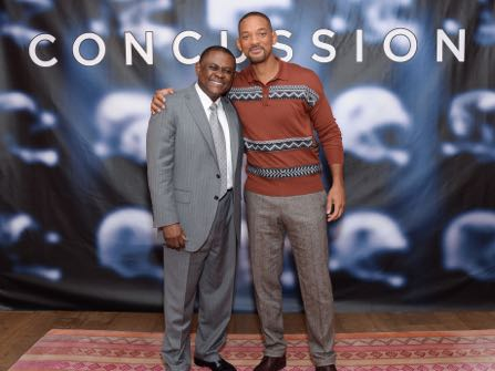 """FILE - In this Dec. 14, 2015, file photo, Dr. Bennet Omalu, left, and actor Will Smith pose together at the cast photo call for the film """"Concussion"""" at The Crosby Street Hotel in New York. In the trailer for the movie """"Concussion,"""" Will Smith, portraying Omalu, says: """"I found a disease that no one has ever seen."""" It's a claim that Omalu, a forensic pathologist, has himself made for years, often even giving a detailed description about how he came to name that disease """"chronic traumatic encephalopathy."""" But Omalu neither discovered the disease nor named it, according to medical journals and concussion researchers who were interviewed by The Associated Press. (Photo by Evan Agostini/Invision/AP, File)"""
