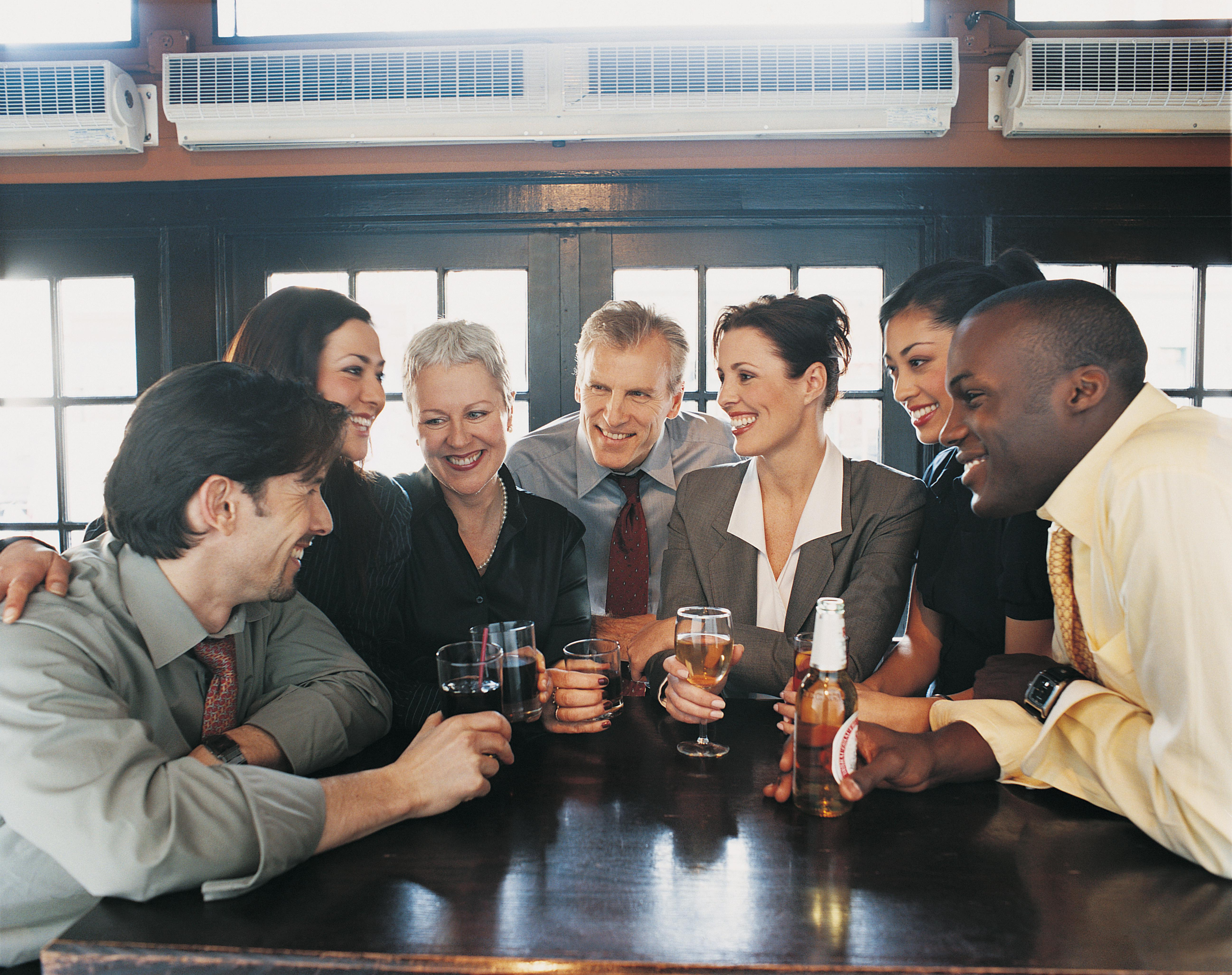 Businessmen and Businesswomen Work Colleagues Enjoying a Drink in a Bar