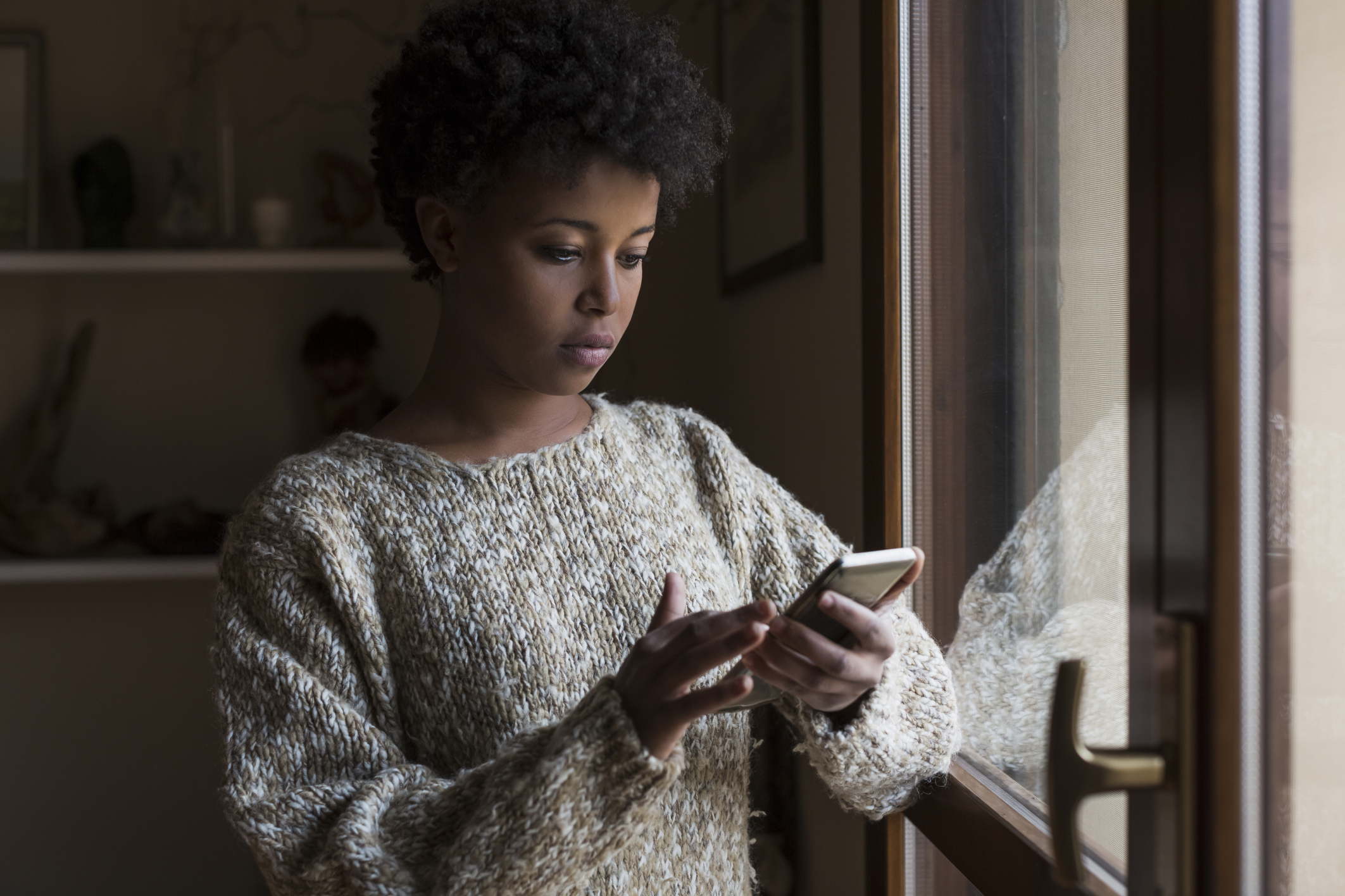 Young woman at the window looking at smartphone