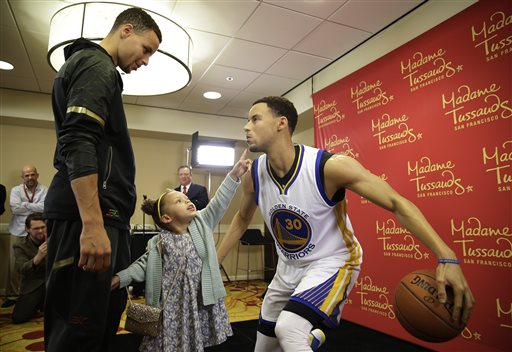 Golden State Warriors guard Stephen Curry, left, watches his daughter Riley as she examines his wax figure by Madame Tussauds after its unveiling Thursday, March 24, 2016, in Oakland, Calif. The figure of the NBA MVP will go on display at Madame Tussauds wax museum at Fisherman's Wharf in San Francisco. (AP Photo/Eric Risberg)