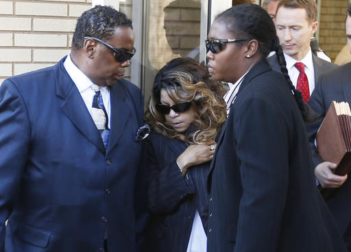 Tyka Nelson, center, the sister of Prince, is escorted by unidentified people as she leaves the Carver County Courthouse Monday, May 2, 2016, in Chaska, Minn. where a judge has confirmed the appointment of a special administrator to oversee the settlement of Prince's estate. The pop singer died on April 21 at the age of 57. (AP Photo/Jim Mone)
