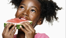 Girl (6-7) looking upwards eating watermelon, close-up